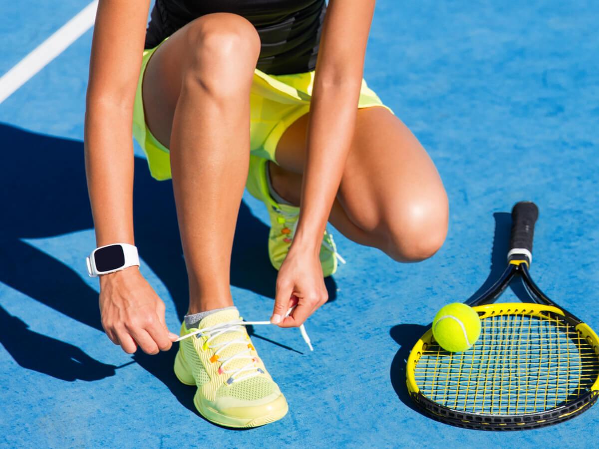 テニスシューズの紐を結ぶ人