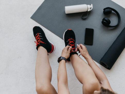 トレーニングマットの上で靴を履く人